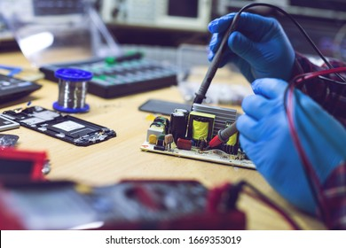 Technician engineer in workshop. Repairman is checking circuit board of electronic device.