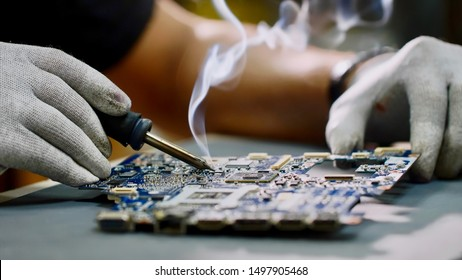 Technician engineer in workshop. Repairman in gloves is soldering circuit board of electronic device on the table, hands close up. He takes tin with a soldering iron and puts it on microcircuit.