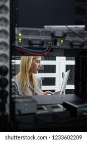 Technician examining server in server room