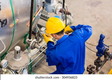 Technician in factory at machine maintenance working with wrench, top view on the man