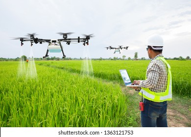 Technician farmer use wifi computer control agriculture drone fly to sprayed fertilizer on the green rice fields, Smart farm 4.0 concept