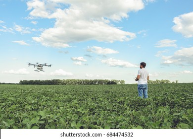 Technician farmer use wifi computer control agriculture drone on green field. Agriculture drone on the green field.