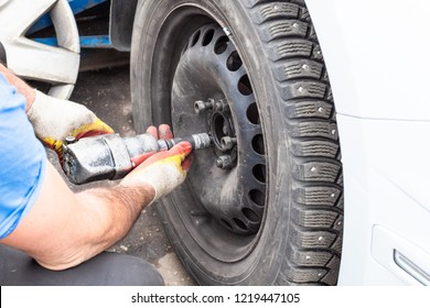 technician fixes a winter car wheel by pneumatic torque wrench outdoors during seasonal replacement of tires