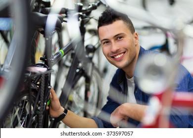 Technician fixing bicycle in repair shop