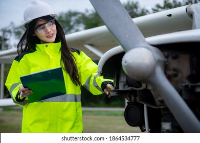 Technician fixing the engine of the airplane,Female aerospace engineering checking aircraft engines,Asian mechanic maintenance inspects plane engine