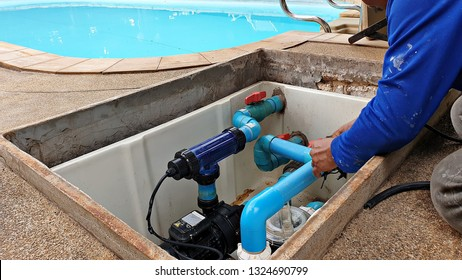 Technician fixing swimming pool water pump. Service and maintenance for swimming pool.