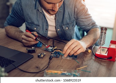 Technician focused on the repair of electronic equipment by soldering iron.