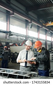 Technicien en vêtements de formation utilisant une tablette lors de l'ingénierie d'une machine industrielle avec un ouvrier en atelier