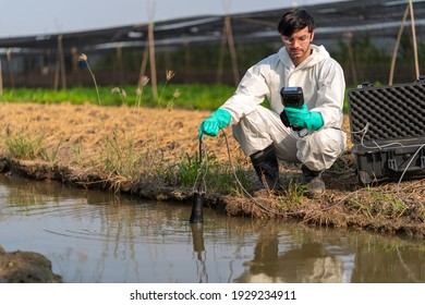A technician in full body protective suit collecting sample of water ,Portable water quality measurement ,water quality for agriculture ,ph checking on field