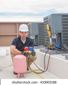 Technician with guages hooked up to a condensing unit.