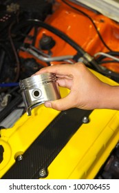 technician hand holding a piston with engine room background