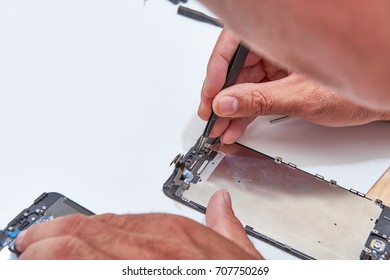 Technician Hand Repairing Cellphone,process of mobile phone repair, isolated on white background,Selective focus