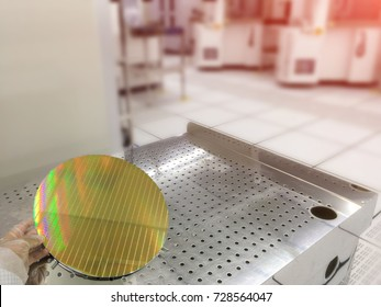 technician hand showing a silicon wafer reflecting different colors;  working at clean room laboratory,