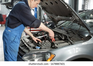 technician hands measure voltage of battery in the car at service station, Maintenance and repair