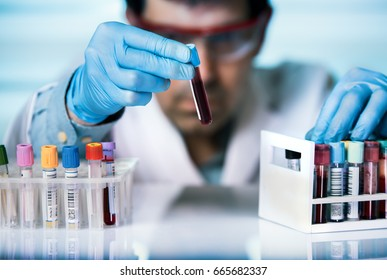 technician of health with blood tubes in the clinical lab for analytical / hand of doctor holding blood sample in tube test for analysis in laboratory