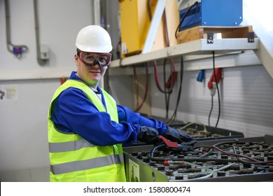 technician in a helmet and safety glasses includes charging batteries for forklifts in the battery room