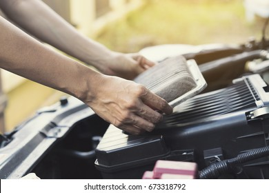 Technician holding dirty air filter for car, maintenance and repair concept