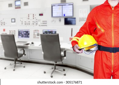 Technician holding hard hat for working at control room of a modern thermal power plant