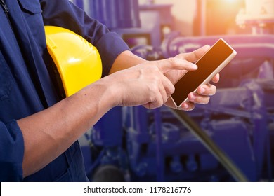 Technician holds smartphone with blank black screen on the background of the machine.