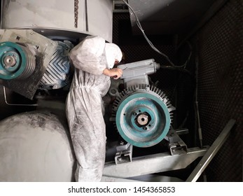 Technician inspection electric motor inside blowers , Have dust suit and mask protect