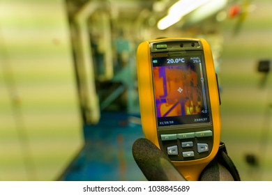 A technician inspects the system in a technical room with a thermal imaging camera