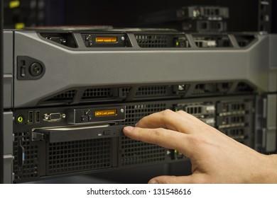 A technician install a 2 unit rack server in a data center.