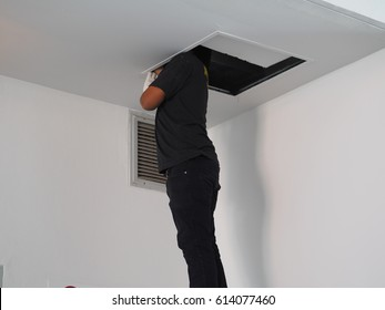 Technician install suspended ceiling in office