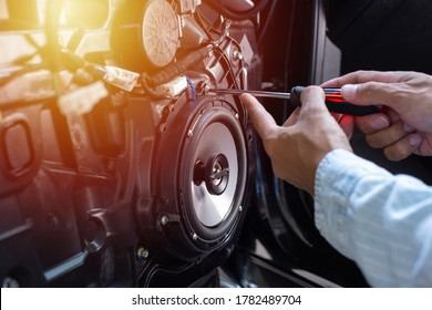 Technician installing the car speaker to the car door. Car audio installation concept.