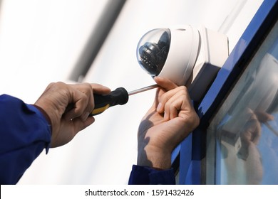 Technician installing CCTV camera on wall outdoors, closeup