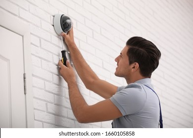 Technician installing CCTV camera on wall indoors