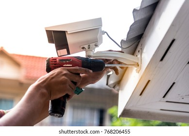 Technician installing CCTV camera on the roof of the house for security