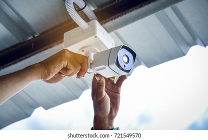 Technician installing CCTV camera for security car park