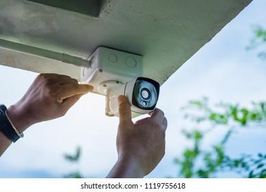 Technician installing CCTV camera system on the corner building