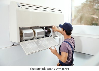 Technician installing and checking air conditioner indoors