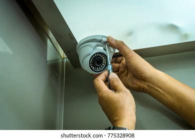 Technician installing dome CCTV camera in elevator.