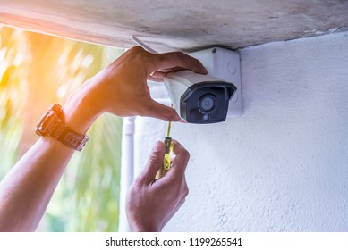 Technician installing IP wireless CCTV camera by screwed for home security system and installed white plastic boxes for safe from water and rain