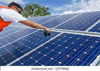 Technician installing solar panels on factory roof
