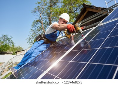 Technician installing solar photo voltaic panel to metal platform using screwdriver on bright blue sky background. Stand-alone solar panel system installation concept.