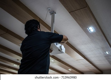 The Technician installing and testing the new projector on the ceiling