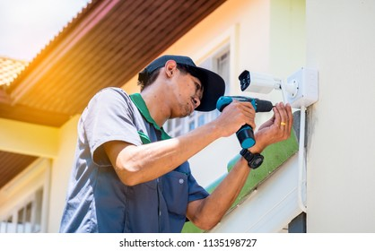 Technician is installing wireless CCTV camera system at house by Cordless battery drill