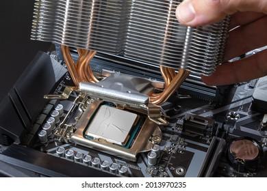 A technician installs an aluminum air-cooled heatsink on a desktop CPU covered with heatsink paste. Air Cooler CPU. PC assembly and modernization