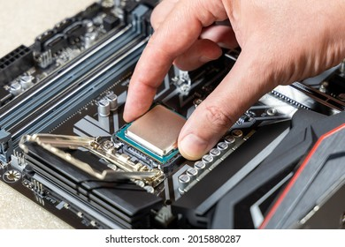A technician installs an Intel i7-9700K CPU in 1151 socket on a Gigabyte motherboard. PC assembly and upgrade concept
