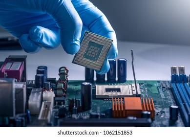 The technician is laying a CPU on the socket of the computer motherboard. the concept of computer, service, electronics, hardware, repairing, upgrade and technology.