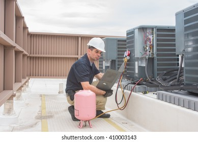 Technician looking at a panel off a condensing unit.