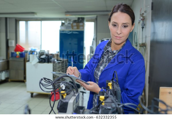 technician maintaining record of rack mounted server on clipboard