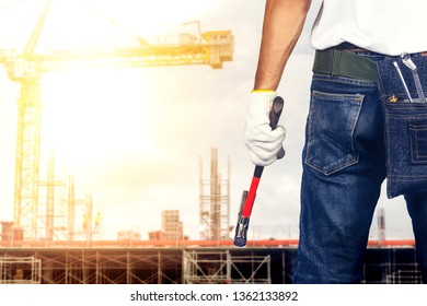 Technician man or engineer holding hammer standing on construction site.Worker inspection or control on working concept.