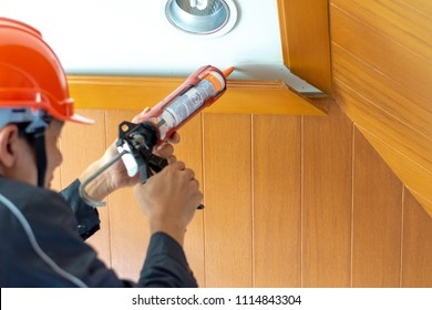 Technician man hand holding glue gun or manual caulking gun to  repair and fix the wooden cornice with the ceiling. Installation or renovation interior concept.