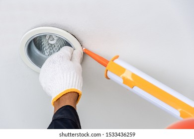 Technician man hand holding glue gun with silicone adhesive or manual caulking gun with polyurethane to repair and fix the lamp light fixture to the ceiling . Installation and maintenance concept.