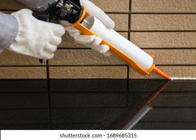Technician man hand holding glue gun with silicone adhesive or manual caulking gun with polyurethane for applying silicone sealant to material . Maintenance concept.