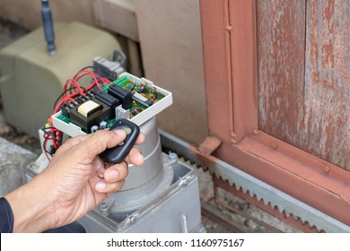 Technician man hand holding the  remote control, testing and checking the function of automatic gate. Maintenance concept.